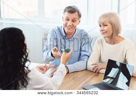 Asthma Treatment. Female Doctor Giving Blue Inhaler To Senior Patient Who Is Sitting With His Mature