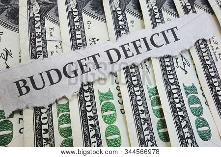 Budget Deficit News Headline On Hundred Dollar Bills  -- Government Spending Concept