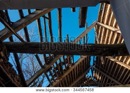 Ruined Roof Of An Old Country House. Inside View. There Are Wooden Rafters, Structural Elements, The