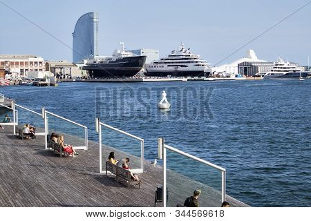 The Tourists Rest Surrounded By Seagulls In The Old Port Of The City Of Barcelona.
