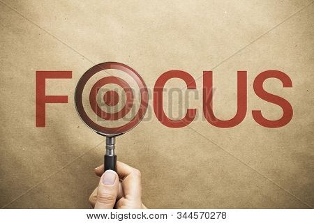 Woman Hand Holding Magnifying Glass Over The Word Focus Written On Paper Background. Target Symbol I