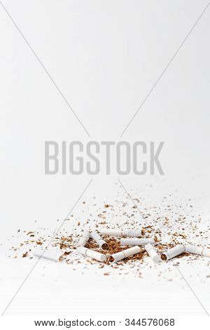 The Concept Of Nicotine Dependence And Tobacco Smoking. Scattered Tobacco And Broken Cigarettes Lie