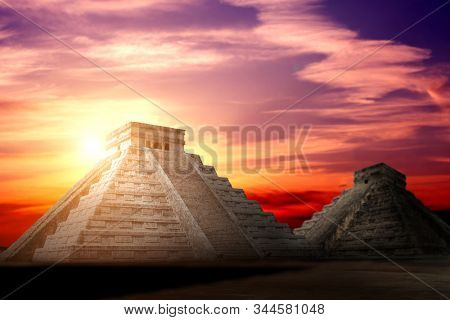 Two ancient Mayan pyramids (Kukulcan Temple) on beautiful dramatic sunset sky background, Chichen Itza, Yucatan, Mexico. UNESCO world heritage site