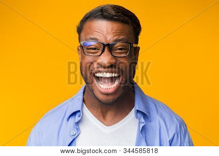 Laughter Concept. Portrait Of Millennial Black Man Laughing Out Loud Looking At Camera Standing Over
