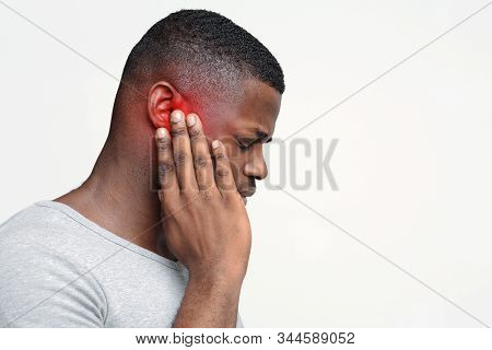 Tinnitus. Profile Of Sick Back Guy Having Ear Pain, Touching His Painful Head, Copy Space