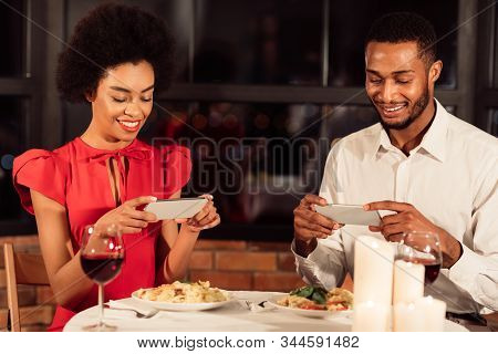 African American Spouses Taking Photo Of Food In Their Plates On Phones Ignoring Each Other During R