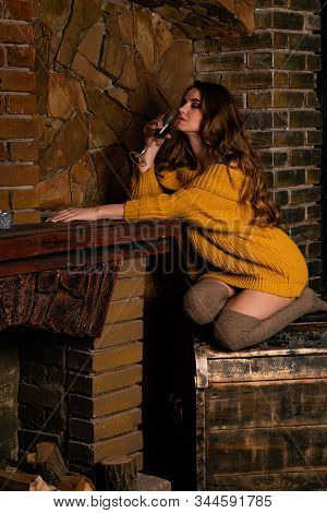 Beautiful Girl Sitting Next To The Fireplace. Luxury Interior Decorated For Christmas With Fir Branc
