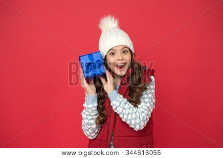 Intrigued With Unexpected Parcel. Xmas Gift Idea. Winter Holidays. Happy Kid Winter Outfit Hold Gift
