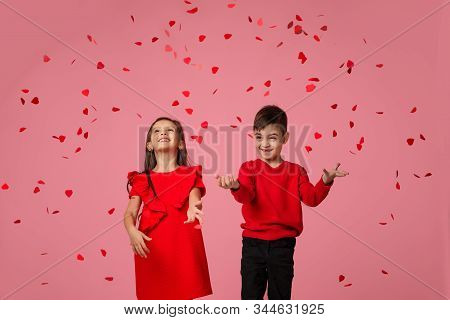 Happy Romantic Little Couple Child Girl And Boy Stand In The Rain Of Flying Rose Petals On Pink Back