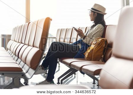 Happy Asian Woman Traveler Wear Eyeglasses And Hat Is Enjoying With Smartphone While Waiting A Fligh