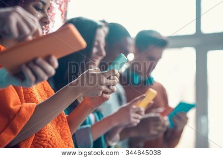 Students Holding Colorful Smartphones While Having Break From Study