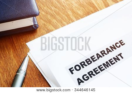 Forbearance Agreement Papers With Pen And Notepad.