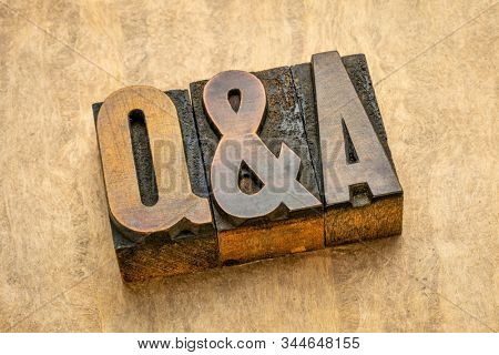 Questions and answers acronym - word abstract in vintage letterpress wood type printing blocks against handmade bark paper, communication and help concept