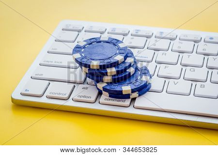 Online Poker. Chips Near Keyboard On Yellow Background