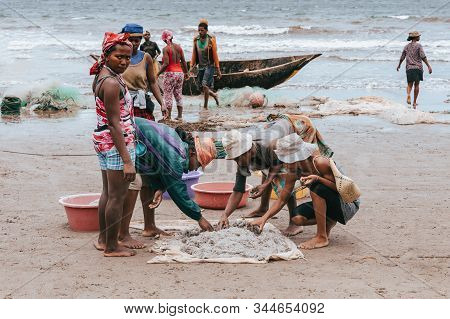 Maroantsetra, Madagascar October 19.2016: Native Woman Sort Catch On Beach After Fishing. Daily Life