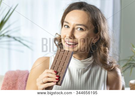 Young Woman Holding A Chocolate Bar To Enjoy The Taste And Are Dieting, Healthy Eating, Feeling Temp