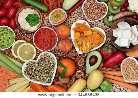 Healthy diet vegan food with grains, nuts, dips, bean curd, fruit, vegetables, legumes & spice. Food high in antioxidants, vitamins, dietary fibre, smart carbs & protein. Plant based diet concept.