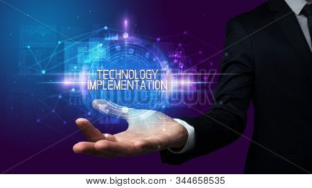 Man hand holding TECHNOLOGY IMPLEMENTATION inscription, technology concept