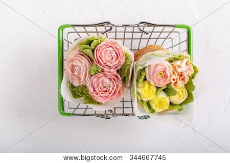 Flower Cupcakes In Small Shopping Basket On White Background. Beautiful Sponge Cup Cakes Decorated W