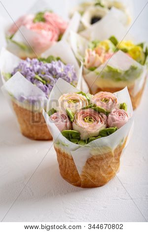 Flower Cupcakes On White Background. Beautiful Sponge Cup Cakes Decorated With Buttercream Roses.