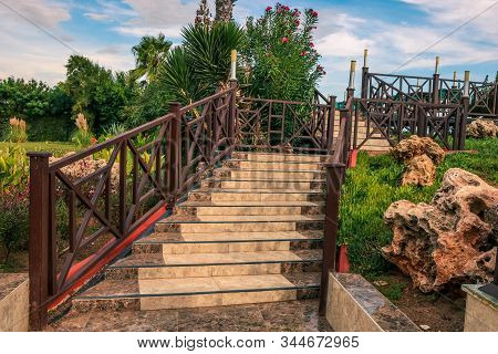 Outdoors. An Old Stone Staircase With Wooden Railings, Leading Upwards. Blue Sky Above. Staircase Wi