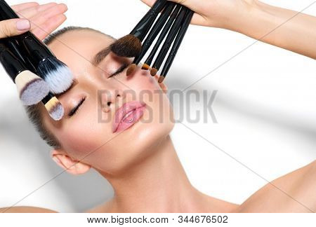 Beauty model girl, makeup artist holding set of make up brushes closeup. Beautiful brunette young woman with perfect skin and nude make-up. Perfect skin closeup. Face contouring makeup. On white