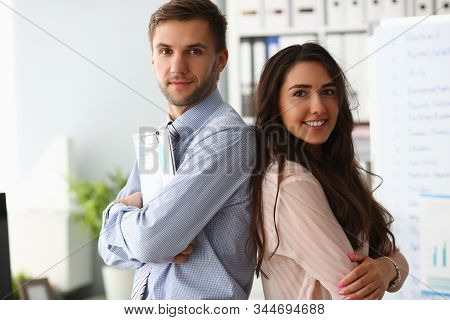 Portrait Of Professionals Standing Back To Back. Happy Co-workers In Office Holding Documents. Succe