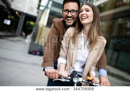 Happy Young Couple Going For A Bike Ride . Young Couple Having Fun In The City.