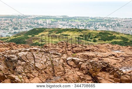 Landscape Of Edinburgh City In Scotland Viewed From Arthurs Seat In Overcast Weather With Red Rocks