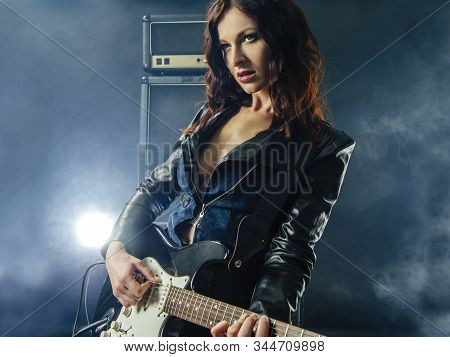 Young Beautiful Woman Playing An Electric Guitar In Front Of Large Amplifier.