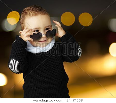 portrait of a funny kid wearing heart sunglasses at a city by night