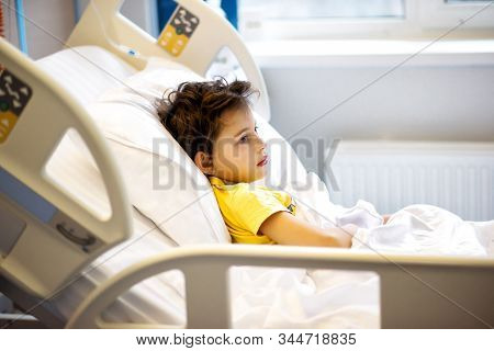 7 Years Old Ill Child In Yellow T-shirt Lying In Hospital Bed After Serious Nasal Surgery. Medical C