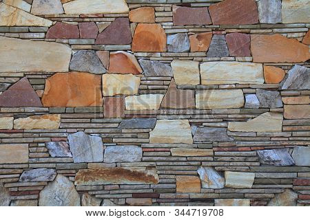 Multy-colored (colorful) Decorative Stone Wall, Texture, Background. Varicolored Natural Stones In T