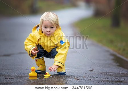 Beautiful Funny Blonde Toddler Boy With Rubber Ducks And Colorful Umbrella, Jumping In Puddles And P