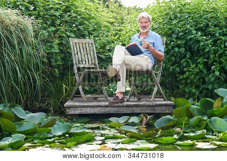 Portrait Of Mature Man Relaxing In Garden Reading Book On Jetty By Lake