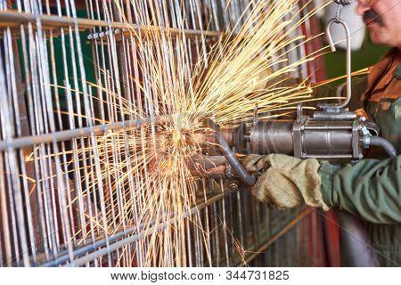 spot welding. industrial factory worker making reinforcement grid