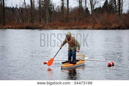 Man Standing In Canoe