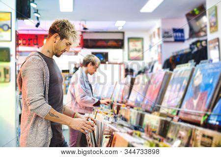 Young Man Choosing Vintage Vinyl Lp In Records Shop