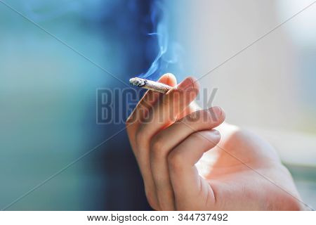 The Man's Hand Holds A Cigarette That Emits Blue Harmful Nicotine Smoke