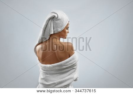 Back View Of Pretty Female With Towel On Head And In Bathrobe Posing, Looking Over Shoulder. Portrai