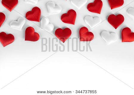 Valentine's day many red and white silk hearts on white background , border frame with copy space, love concept