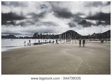 People On The Beach On A Cloudy Day. Brazilian Paulista Seacoast At Praia Da Enseada Beach - Guaruja