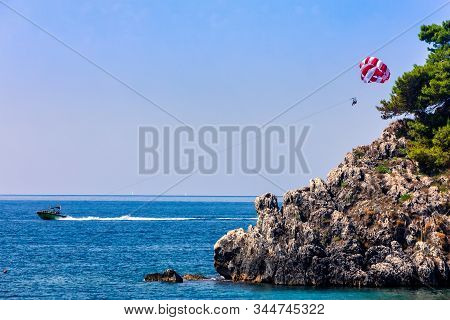 Parachute Behind A Boat On A Summer Holiday Beach In Parga Epirus, Greece, Europe.