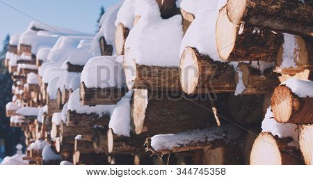 A Woodpile Of Chopped Lumber In The Forest Covered With Snow In Winter.