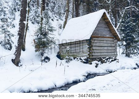 View At Wooden Buiding In Winter Forest, Snow Is All Around. Day Time, Good Background. Winter Fores