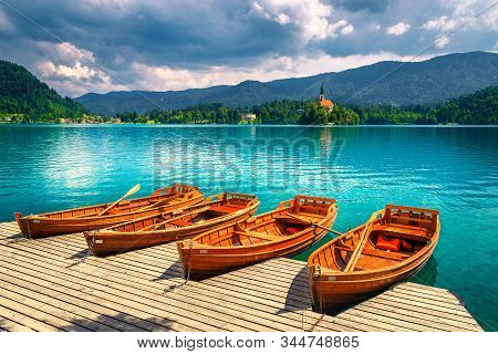 Old Wooden Rowing Boats Moored At The Pier On The Lake Bled. Gorgeous Pillgrimage Church And Small I