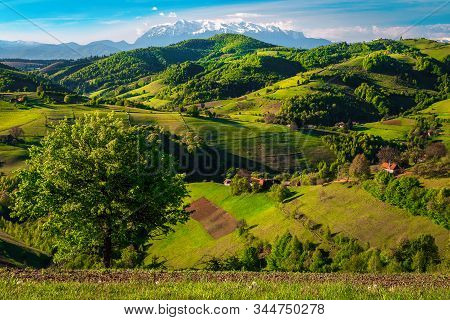 Stunning Spring Coutryside Landscape With Houses On The Slopes And High Snowy Mountains In Backgroun