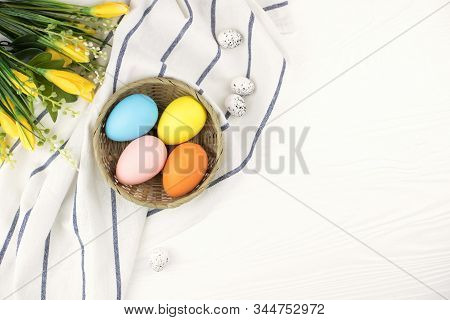 Pastel Colored Eggs In The Nest With The Posy Of Yellow Flowers On White Wooden Background. Easter H