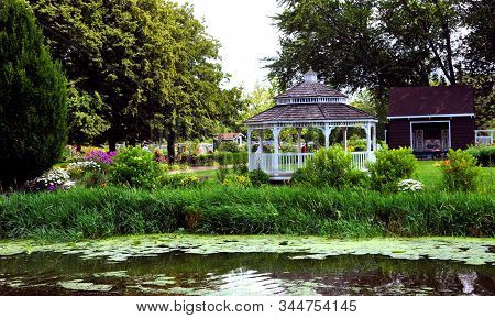 Two Men Work To Maintain The Beautiful Gardens At Windmill Island Gardens In Holland, Michigan.  Whi