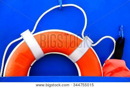 Bright Orange Lifering Sits In Metal Pocket Against Lighthouse.  Preserver Is Present For Emergencie